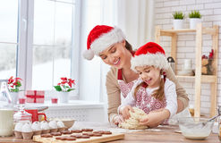 Cooking Christmas biscuits. Mother and daughter cooking Christmas biscuits Royalty Free Stock Photography