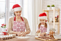 Cooking Christmas biscuits. Mother and daughter cooking Christmas biscuits Stock Image