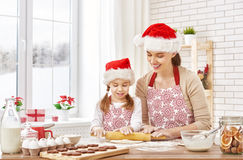 Cooking Christmas biscuits. Mother and daughter cooking Christmas biscuits Royalty Free Stock Images