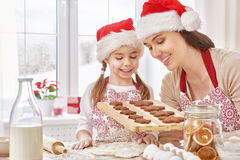 Cooking Christmas biscuits. Mother and daughter cooking Christmas biscuits Royalty Free Stock Photo