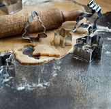 Cooking Christmas cookies with  cookie cutters. On a dark table Royalty Free Stock Photo