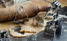 Cooking Christmas cookies with  cookie cutters. On a dark table Royalty Free Stock Photography