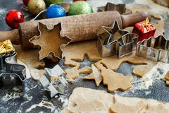 Cooking Christmas cookies with  cookie cutters. On a dark table Stock Photos