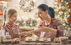 Cooking Christmas cookies. Merry Christmas and Happy Holidays. Family preparation holiday food. Mother and daughter cooking cookies Stock Photo