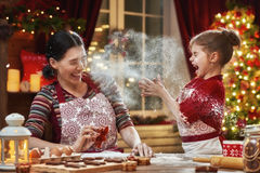 Cooking Christmas cookies. Merry Christmas and Happy Holidays. Family preparation holiday food. Mother and daughter cooking Christmas cookies royalty free stock images