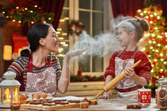 Cooking Christmas cookies. Merry Christmas and Happy Holidays. Family preparation holiday food. Mother and daughter cooking Christmas cookies royalty free stock image