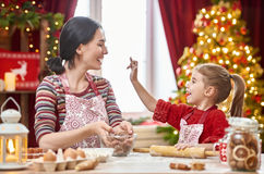 Cooking Christmas cookies. Merry Christmas and Happy Holidays. Family preparation holiday food. Mother and daughter cooking Christmas cookies Royalty Free Stock Photo