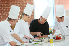 Cooking class with chef. Chef training students in restaurant kitchen Royalty Free Stock Images