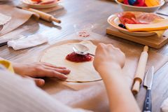 Cooking class, culinary. Food and people concept, desktop getting ready for work, ingredients for italian pizza. Kid hands. In work progress Royalty Free Stock Photos