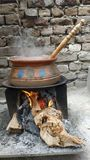 Cooking in clay pot. Woman cooking meat clay pot village kitchen fire wood stove smoke dung cattle royalty free stock photo