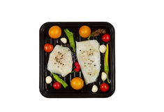 Cooking Cod Fish in baking pan. Top view of fresh raw Cod Fish Fillets in cooking pan with tomatoes, garlic, peppers and peppercorn salt isolated on white Stock Images