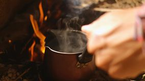 Cooking coffee on a campfire in the foggy forest. Coffee is boiling on the bonfire in the small pot stock video