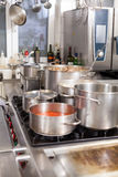 Cooking in a commercial kitchen. With large stainless steel pots filled with stew and vegetables on a central gas hob Stock Images