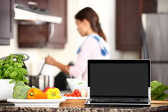 Cooking and computer laptop concept. Blank pc monitor screen in focus with cooking woman in kitchen royalty free stock image