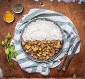 Cooking concept Cooked turkey onions and spices lined with half the rice in a pan on a striped napkin on rustic wooden backgr Stock Photography