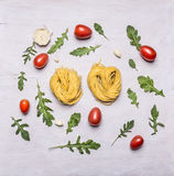 Cooking Concept nest pasta Cherry tomatoes arugula and garlic rustic wooden background top view Stock Photography