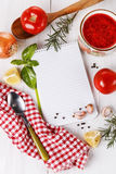 Cooking concept. Recipe book and ingredients for cooking tomato Stock Images