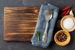 Cooking concept. Vintage cutting board with spices and cutlery. On dark stone background. Copy space royalty free stock images