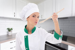 Cooking concept - young woman in chef uniform tasting something Royalty Free Stock Image
