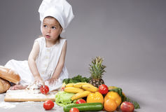 Cooking Concepts. Little Caucasian Girl Posing as Cook with Vegetables. Stock Image