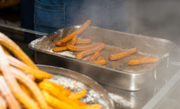 Cooking confectionery product Churros near fryer with boiling oi. Cooking confectionery product Churros near fryer and prepared Churros Stock Images