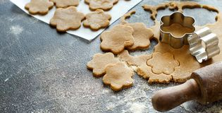 Cooking cookies with  cookie cutters. On a dark table Royalty Free Stock Image