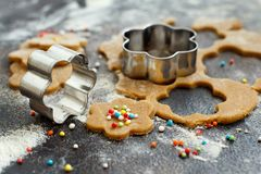 Cooking cookies with  cookie cutters. On a dark table Royalty Free Stock Photos