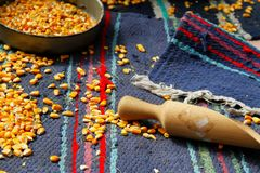 Cooking corn. A few grains of corn placed in a mess on the colorful carpets Stock Photo