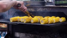 Cooking corn on grill close-up. Man turns over corn so it doesn`t burn on grill. Cooking corn on grill close-up. Man turns over corn so it doesn`t burn on the stock footage