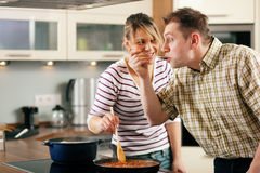 Cooking couple - tasting the sauce royalty free stock images