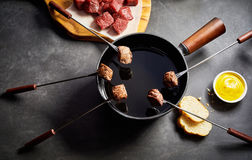 Cooking Cubes of Beef in Fondue Pot of Hot Oil Royalty Free Stock Image