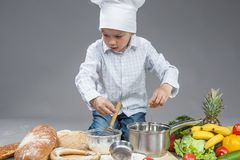 Concentrated Caucasian Boy Mixing Fresh Egg in Saucepan Royalty Free Stock Photography