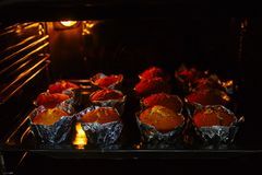 Cooking cupcakes at home. Baking on a baking sheet in the oven.  royalty free stock photo