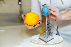 Cooking cupcakes at home. Girl grate orange zest stock images