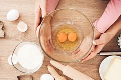 Cooking cupcakes in kitchen. Female and children`s hands hold bowl with eggs. stock photos