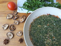 Cooking dandelion leaves omelette with mushrooms. Shiitake, tomato and onion stock images