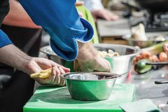 cooking De chef-kok snijdt greens in de keuken royalty-vrije stock foto's
