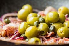 Cooking delicious dish, bacon, red onions, green olives, capers Stock Photo