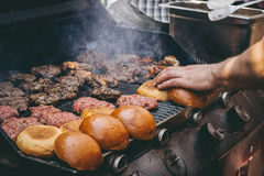 Cooking delicious juicy meat burgers and buns on the grill outdoor. Royalty Free Stock Photography