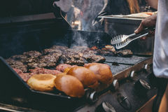 Cooking delicious juicy meat burgers and buns on the grill outdoor. Royalty Free Stock Photo