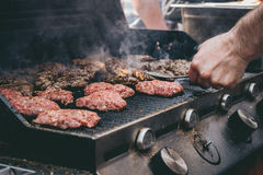 Cooking delicious juicy meat burgers on the grill outdoor. Selective focus Stock Photography