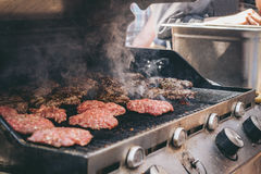 Cooking delicious juicy meat burgers on the grill outdoor Royalty Free Stock Photo