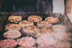 Cooking delicious juicy meat burgers on the grill outdoor Royalty Free Stock Photography