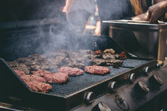 Cooking delicious juicy meat burgers on the grill outdoor Stock Photo