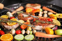 Cooking delicious meat and vegetables on barbecue grill. Closeup stock photos