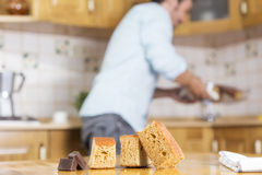 After of cooking a delicious sponge cake. A man is putting a sponge freshly baked cake in a kitchen and three pieces of cake and bits of chocolate is in a wood stock images
