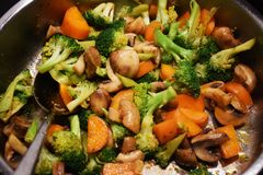 Cooking Delicious Stir Fried Vegetables. Stir Fried Vegetables are cooked in a pan together with oil, broccoli, carrots, mushrooms, spices, seasonings and garlic royalty free stock photo