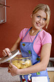 Cooking the dinner. Portrait of young pretty woman in the apron with the jar in her hands Stock Photos