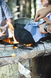 Cooking dinner on campfire. Cooking food in pot on fire at camping place Stock Photo
