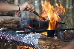 Cooking dinner on campfire. Cooking food in pot on fire at camping place Royalty Free Stock Photos